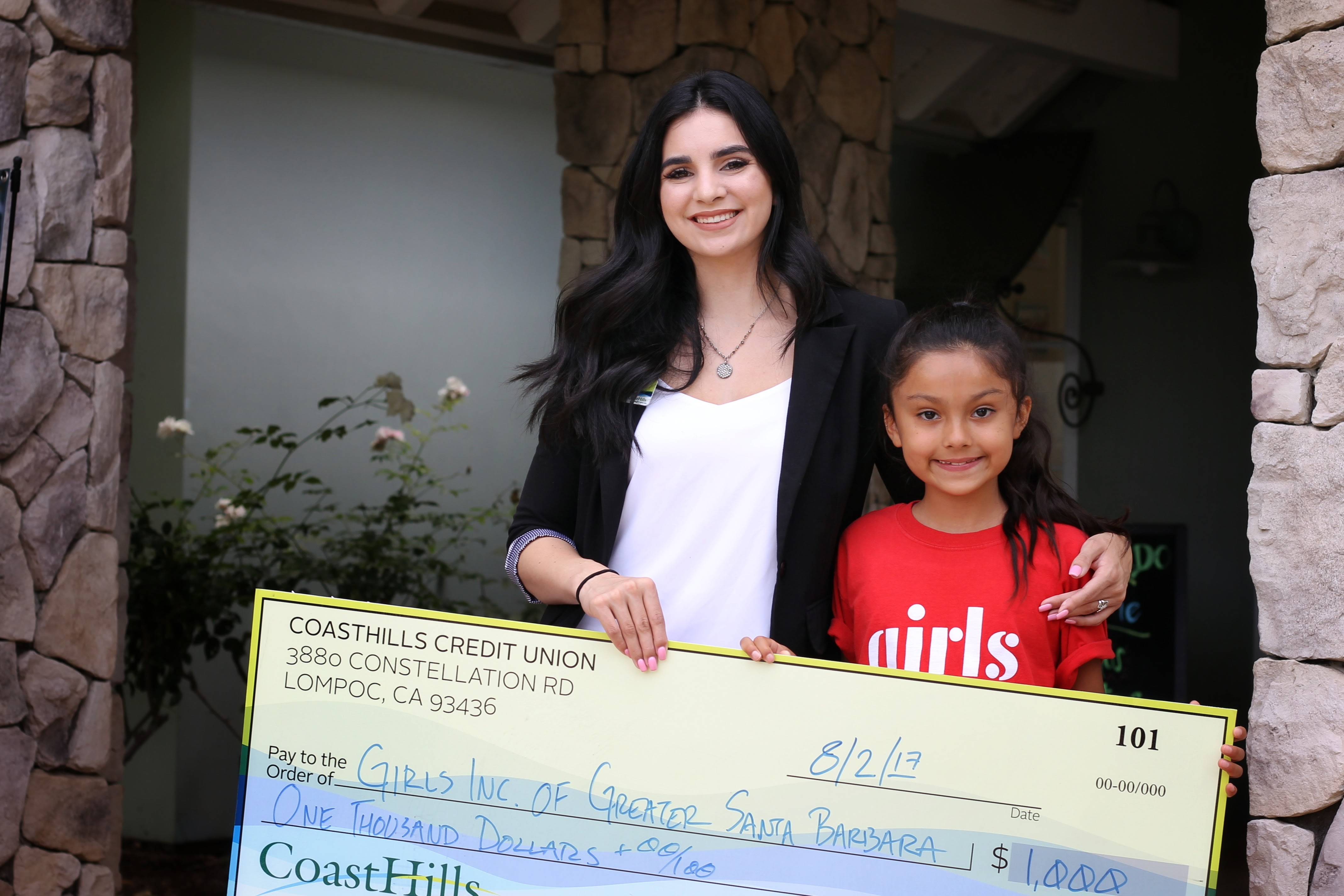 CoastHills Credit Union corporate employee Selenda Diaz and her sister Ava present Girls Inc. of Santa Barbara a check for $1,000 from the Credit Union's employee giving program.