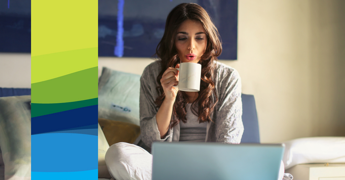 A woman sips from a mug while using a laptop computer on her bed.