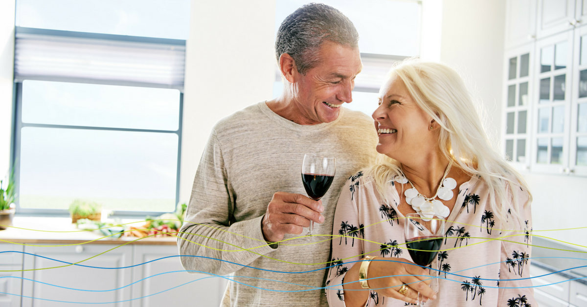 This middle-aged couple is enjoying a glass of wine in their kitchen.