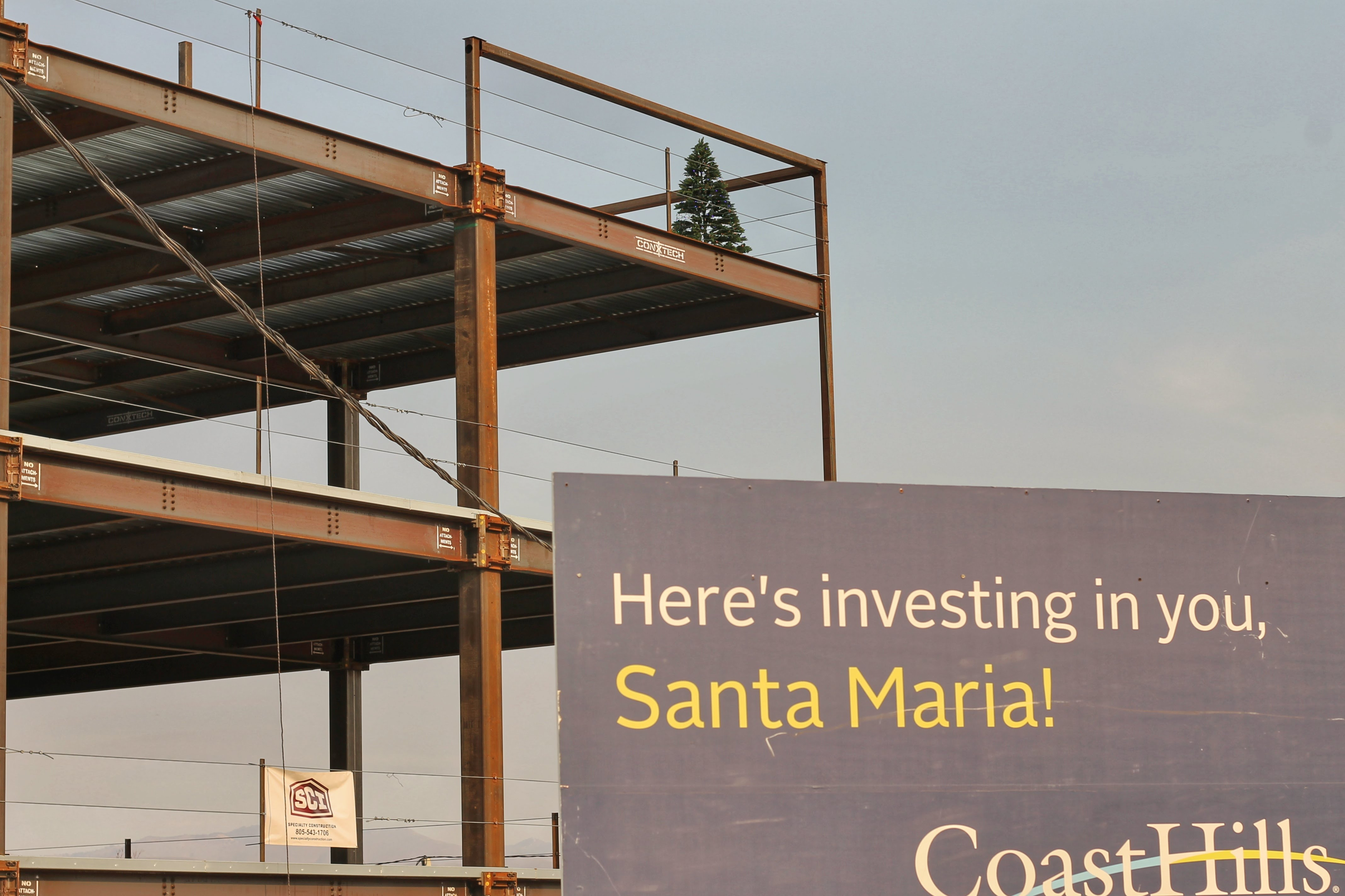 A Christmas tree sits atop the construction site of the CoastHills Credit Union headquarters project.