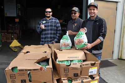 CoastHills employee Tristan King poses with his donation of $1,000 of turkeys to the Santa Barbara County Food Bank.